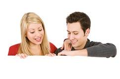 Valentine : Le couple de sourire regarde vers le bas la carte blanche Image stock