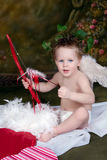 Valentine Love. Young boy as Cupid with wings holding Bow and Arrow royalty free stock photography