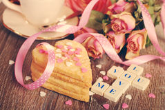 Valentine love declaration in vintage style. Love words made of scrabble letters ,dried roses  and heart shaped cookies with sprinkles  for valentine on wooden Royalty Free Stock Photos