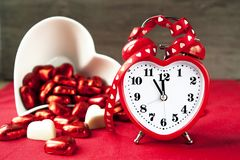 Valentine love heart shaped red love clock with sweet chocolates. Valentine love heart shaped red clock with chocolates. Time for sweet love. Indoors closeup Stock Photography