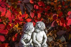 Romantic, valentine statue with two kissing children. Valentine love, kissing statue and red leaves stock photos
