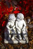 Romantic, valentine statue with two kissing children. Valentine love, kissing statue and red leaves stock photo
