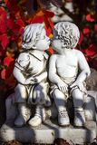 Romantic, valentine statue with two kissing children. Valentine love, kissing statue and red leaves stock image