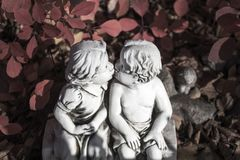 Valentine love, kissing statue and red leaves. In the sunshine royalty free stock photos
