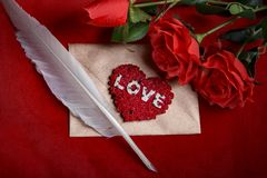 Valentine love letter, roses, quill and envelope. Valentine`s day celebration with romantic items: sealed love letter, a rose, a writer`s quill on a dark red Royalty Free Stock Photography