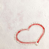 Valentine love red heart shape in snow on red background. Royalty Free Stock Images