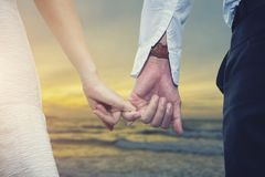 Valentine, love and wedding concept. Closeup of loving couple ho. Lding hands while walking on the beach at sunset. Picture for add text message. Backdrop for Royalty Free Stock Photos