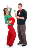 Valentine love, young adults. Two casual dressed young adults, teenage man holding rose flower and woman in love. studio shot Stock Photos