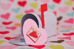 Valentine mailbox and hearts. An empty white mailbox with its red flag up  on a background of hearts representing Valentine's day.  A pink Valentine is in front Royalty Free Stock Image