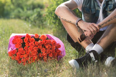 Valentine male with bunch of roses sitting on grass. Bouquet of roses on the grass close to guy Royalty Free Stock Photo