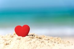 Valentine and Marry Concept. Sigle red hearts couple lovers for married on the sand summer beach,. Blue background royalty free stock image