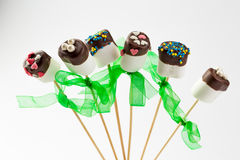 Valentine marshmallow pops on white background. Chocolated marshmallows on sticks with green band isolated Royalty Free Stock Photography