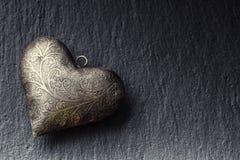 Valentine Metal-Herz auf einem Granitbrett Das silberne Herz des Valentinsgrußes zwei mit Verzierungen Herz von Liebesvalentinsgr Lizenzfreie Stockfotografie