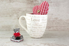 Valentine miniature teddy bear and red heart on wooden backgroun Stock Images