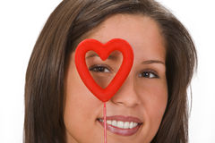 Valentine monocle. Smiling woman looking through a red heart-shaped monocle.Shot with Canon 70-200mm f/2.8L IS USM Stock Photo