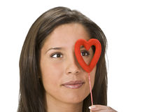 Valentine monocle. Smiling woman looking through a red heart-shaped monocle Stock Photo
