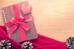 Valentine ou thème d'amour, coeur de feutre se reposant sur le carnet enveloppé Photos stock