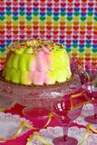 Valentine Party Cake. A pink and yellow iced cake on a table decorated with yellow ribbons, pink glasses and white paper doilies against a multi-colored heart Royalty Free Stock Photos