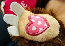 Valentine Paw - rosa tyghjärta med broderat på foten av ett välfyllt leker med en välfylld hjärta som säger FÖRÄLSKELSE i backgro Arkivfoto