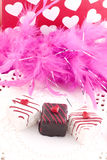 Valentine Petit Fours. Three Valentine Petit Fours on a plate with a pink feather boa and heart background, vertical with copy space Stock Photos