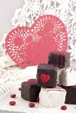 Valentine Petit Fours with Red Heart. A plate of red Valentine Petit Fours with red heart doily with copy space, vertical with selective focus Royalty Free Stock Photos