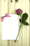 Valentine pink rose and greeting card on wood background. Stock Image