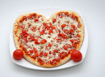 Valentine pizza. A heart-shaped pizza with red topping served on white plate, two small tomatoes as decoration Royalty Free Stock Photo