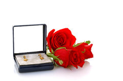 Valentine present. Valentine earrings in box surrounded by red roses, isolated on white Royalty Free Stock Photography