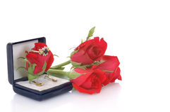 Valentine present. Valentine earrings and ring surrounded by red roses Stock Photo