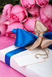 Valentine present with note. And roses in background Stock Photo