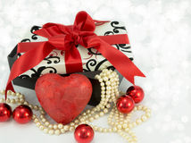 Valentine red heart. Red heart in front of a gift box with pearls flowing out of it Stock Images