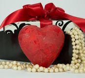 Valentine red heart. Red heart in front of a gift box with pearls flowing out of it Royalty Free Stock Image