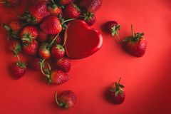 Valentine red heart and strawberry on red background Stock Photos