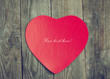 Valentine red paper on wooden boards. Royalty Free Stock Photography