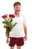 Valentine Roses for You. Scruffy looking middle aged guy in his underwear holding a bouquet of red roses for Valentines Day. Isolated on white royalty free stock image