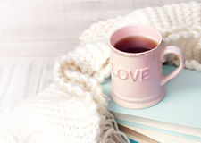 Valentine`s background. Coffee tea mug books knits on wood. Pink coffee tea mug on stack of books with knits vintage background empty space for text. Valentine` Royalty Free Stock Photos