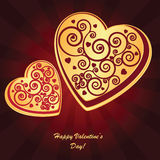 Valentine's background with two hearts. Valentine's background with two gold hearts with ornament on dark phone with rays Royalty Free Stock Image