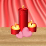Valentine`s candles. Red valentine`s candles with pink hearts on a wood table Stock Images