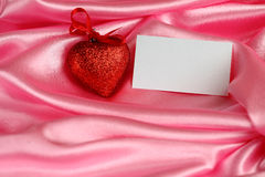 Valentine`s card. With red heart on pink satin stock photo