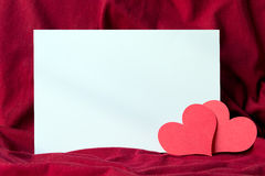 Valentine's card. Blank white paper on red cloth with two red heart shapes Stock Photo