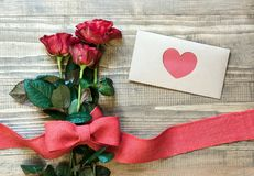 Valentine`s card. Bouquet red rose and envelope with love. View from above. Copy space. Flat lay. Mother day Royalty Free Stock Photo