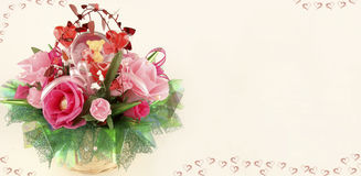Valentine`s card with candy basket. On this horizontal image on the left side of this card is image of candy basket with pink and red roses, green leaves and red Stock Image
