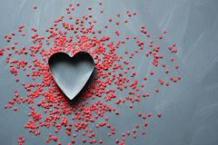 Valentine`s card concept with sweet red hearts sprinkling on gray background. Copy space. View from above. Royalty Free Stock Image