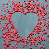 Valentine`s card concept with sweet red hearts sprinkling on gray background. Copy space. View from above. Stock Photography