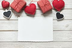 Valentine`s card. Red decor, hearts, gifts, clothespin with white sheet for your text on white wooden board. View from above. Royalty Free Stock Photography