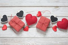 Valentine`s card. Red decor, hearts, gifts on white wooden board and space for text on clothespin. Top view. Banner. View from ab. Valentine`s card. Red decor Royalty Free Stock Images