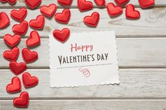 Valentine`s card. Red textile hearts with sheet and wishes on white wooden board. View from above. Royalty Free Stock Image