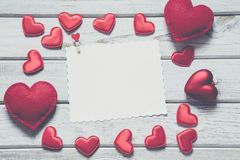 Valentine`s card. Red textile hearts with sheet for your text on white wooden board. Vintage effect. Valentine`s card. Red textile hearts with sheet for your Royalty Free Stock Photography