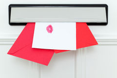 Valentine's cards delivery. Valentine's cards coming through the letterbox, one sealed with a kiss Stock Photo