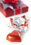 Valentine's Chocolates. Heart Shaped Valentine's Chocolate in red reflective wrapper with gift box in background on white Royalty Free Stock Photography